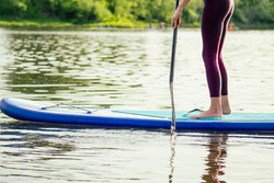 Stand up paddle boarding on a quiet sea lake , close-up of legs and water splash