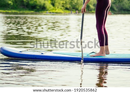 Stand up paddle boarding on a quiet sea lake , close-up of legs and water splash Stock photo ©