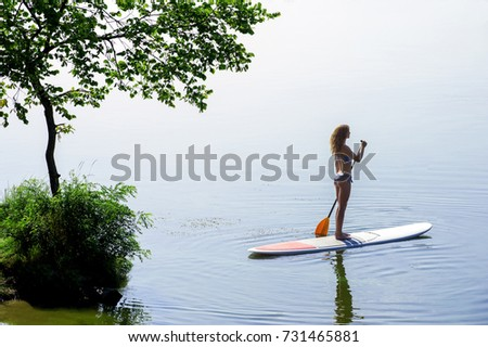 Stand up paddle boarding on blue river. Young woman in bikini with perfect body on board. Beautiful silhouette