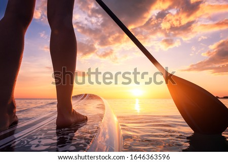 Stand up paddle boarding or standup paddleboarding on quiet sea at sunset with beautiful colors during warm summer beach vacation holiday, active woman, close-up of water surface, legs and board Stock photo ©