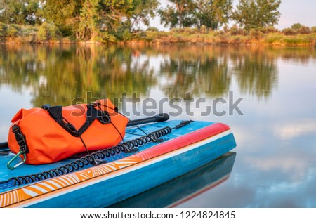 Stand up paddleboard with a paddle, safety leash and waterproof duffel on a shore of calm lake in northern Colorado, summer scenery