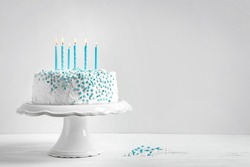 Stand with birthday cake and candles on table against light wall