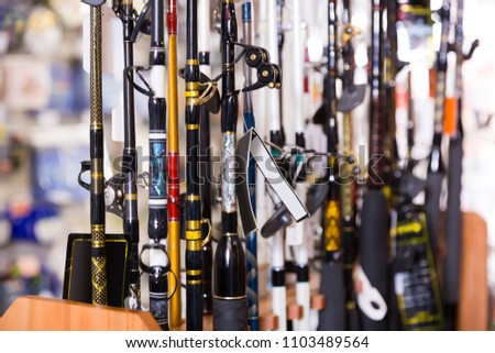 stand with diverse fishing rods in the sports shop indoor