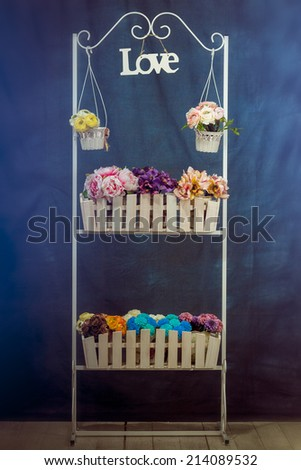 stand with flowers, flowers on the table wooden desk with artificial flowers, fence