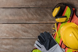 Standard construction safety equipment on old wooden background. top view, safety first concepts