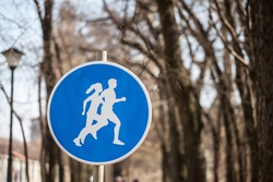 Standard European roadsign, a blue circle with the icon of two people running, indicating the presence and the crossing of a running track used for sports and working out.