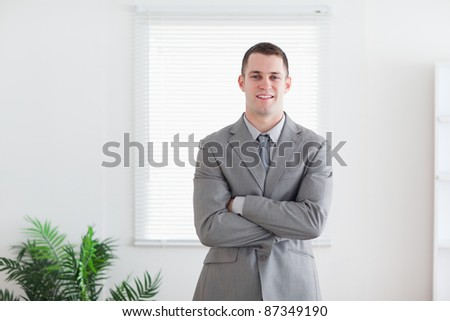 Standing and smiling businessman with his arms folded