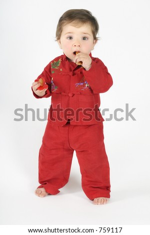 Standing baby teething on a rusk and holding a pacifier in the other hand.