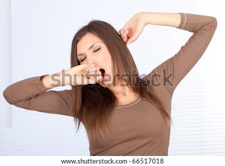 standing beautiful woman in brown blouse, yawning and stretching
