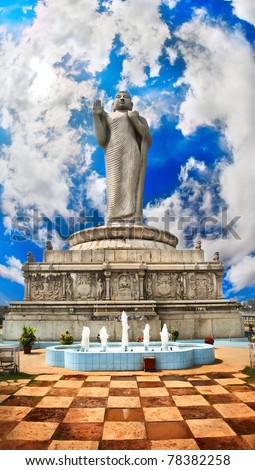 Standing Buddha statue on water in Hyderabad, Andhra Pradesh, India. Floor like a chess desk and fountain near by