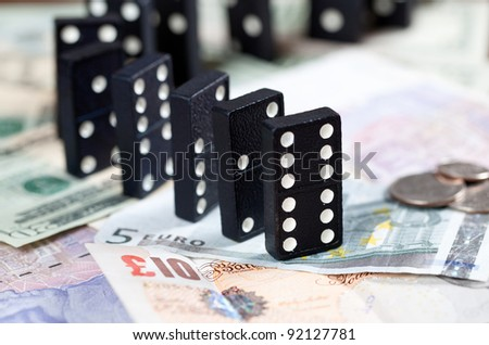Standing dominoes on pound, euro and dollar bank notes illustrating banking crisis