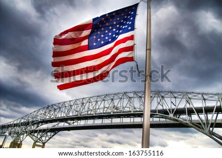 Standing Guard.  Old glory stands guard over an international border crossing. The background contains the Blue Water Bridges, which are the second busiest border U.S. and Canadian border crossing.