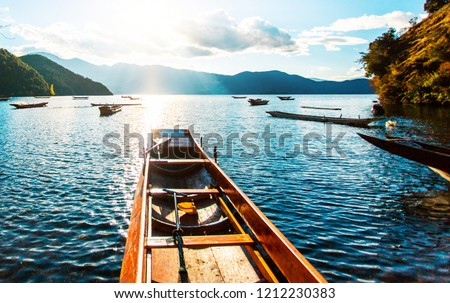 Standing in a canoe overlooking the vast lake and sunset landscape in Lugu Lake, Yunnan Province, China