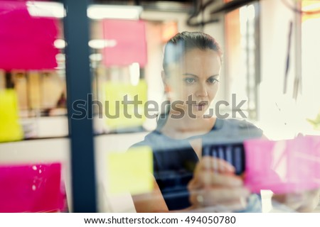 Standing in front of glass wall young business woman with post it stickers.