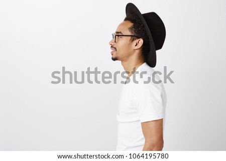 Standing in queue to grab coffee. Studio shot of stylish urban dark-skinned hipster standing in profile in glasses and trendy hat, being pleased and relaxed while waiting for order over gray wall