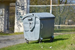 Standing iron garbage bin near fence on sunny day