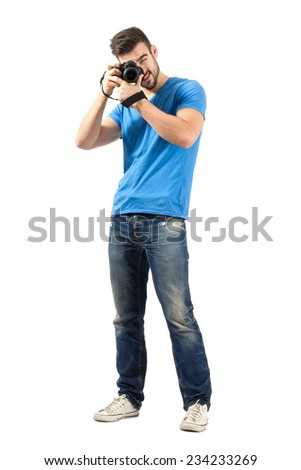 Standing man focusing lens of dslr looking at camera. Full body length portrait isolated over white background. #234233269