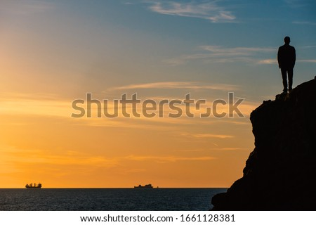 Standing man silouette on a rock in front of the sea at sunset. Conceptual image for future projects with copy space. Stock photo ©