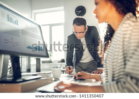 Standing near assistant. Mature businessman wearing glasses making some notes standing near assistant #1411350407