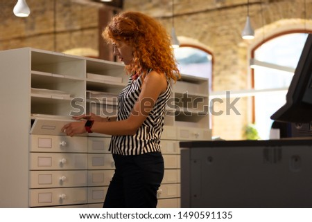 Standing near drawer. Busy red-haired curly businesswoman standing near drawer #1490591135