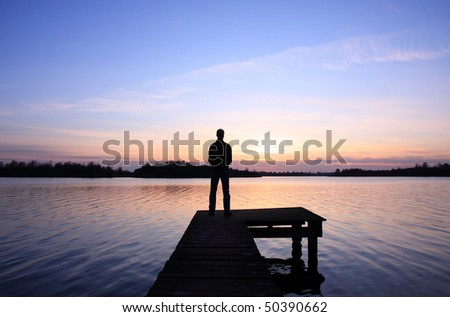 Standing on a small jetty looking at a spring sunset over a Dutch lake. - stock photo