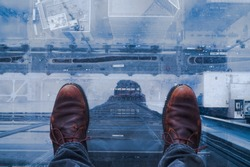 Standing on glass floor on edge of skyscraper in Chicago and looking down