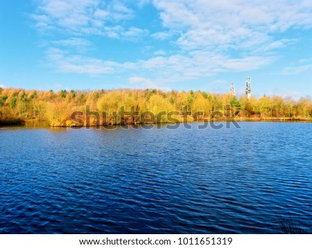 Standing on the banks of Vicar Water, looking across the rippled water at the dense woodland partially hiding the two winding towers of Clipstone colliery