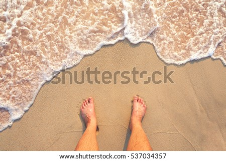Standing on the beach with ocean wave cover the leg ; looking from top #537034357
