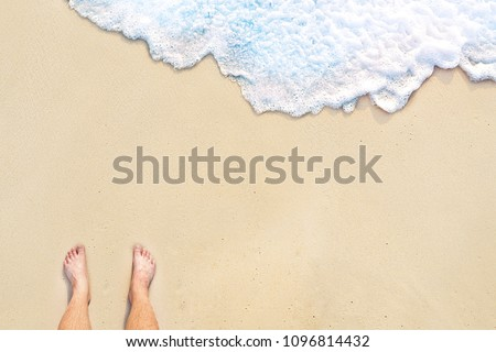 standing on the clean white sandy beach with wave motion coming to the foot