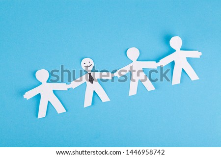 Standing out from the crowd concept, paper people on a blue background. Individuality, uniqueness, positive