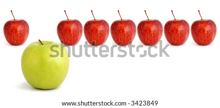 Standing out from the crowd...green apple stands out from a row of red apples.  Business concepts include leadership, individuality, creativity, lateral thinking.