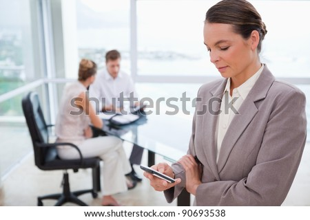 Standing real estate agent with cellphone and sitting clients behind her