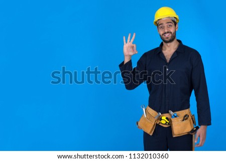 Standing repairman wears overalls-wearing raising hand gesturing ok sign smiling on blue background. #1132010360