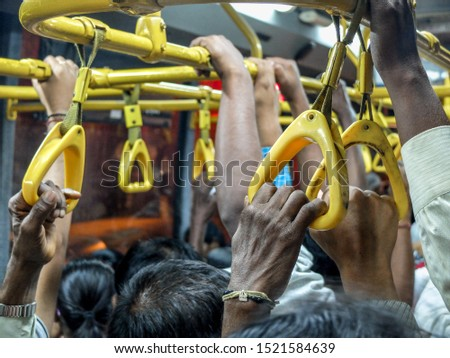 Standing room only and closeup of passengers hands gripping straps and railings on a full, hot early evening bus from central Mysuru (formerly Mysore) bus station to nearer the outskirts of the city. Foto stock ©