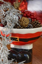 Standing Santa ceramic bowl containing Christmas/holiday decor of pinecones, berries, and glittery foliage