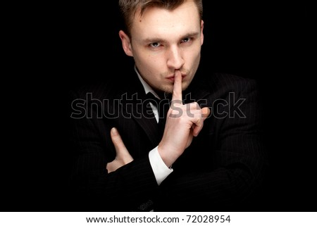 standing serious businessman in black suit, with crossed arms, keeping silence, black background