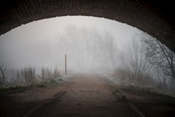 Standing under dark arched old bridge on creepy eerie footpath with fog and mist surrounding.  Spooky atmosphere all alone with no people, thick fog trees hidden in the mist. Selective focus on ground
