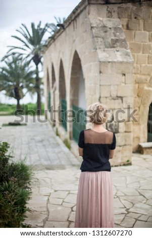 Standing woman in black mohair and tulle sweater and pink skirt in exotic environment