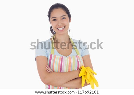 Standing woman smiling and wearing apron while holding rubber gloves