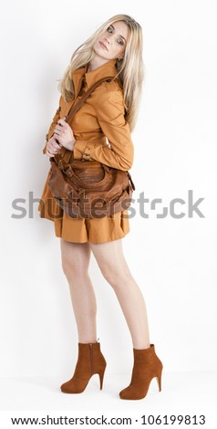 standing woman wearing coat and fashionable brown shoes with a handbag - stock photo