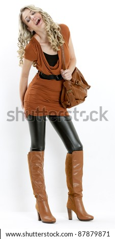 standing woman wearing fashionable brown boots with a handbag - stock photo