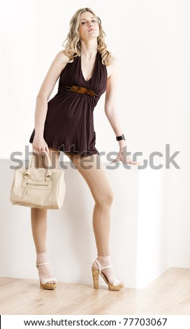 standing woman wearing summer clothes and shoes with a handbag