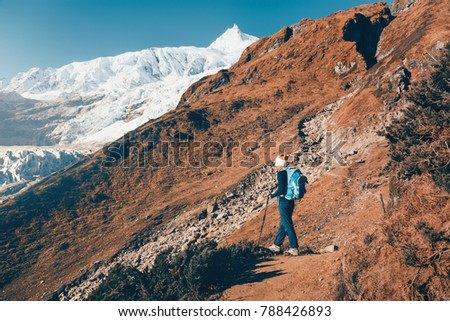 Standing woman with backpack on the mountain trail against snow covered rocks at sunset. Landscape with girl, high mountains with snowy peaks, path, blue sky in Nepal. Travel. Vintage style. Nature