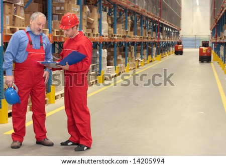 standing workers in warehouse reading invoice