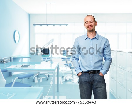 standing young businessman in modern office
