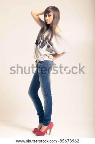 Standing young woman wearing jeans and t-shirt with an inscription love