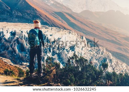 Standing young woman with backpack on the mountain peak against beautiful mountains and glacier at sunset. Landscape with girl, rocks with snowy peaks at bright sunny day in Nepal. Travel.Trekking #1026632245