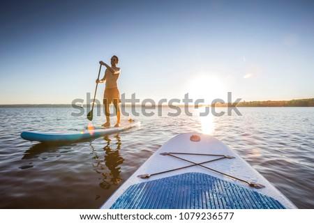 Standup paddler at the lake during sunset Stock photo ©
