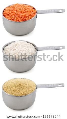 Staple ingredients - lentils, white rice and cous-cous - in cup measures, isolated on a white background