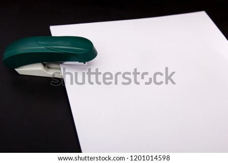 stapler and a sheet of paper